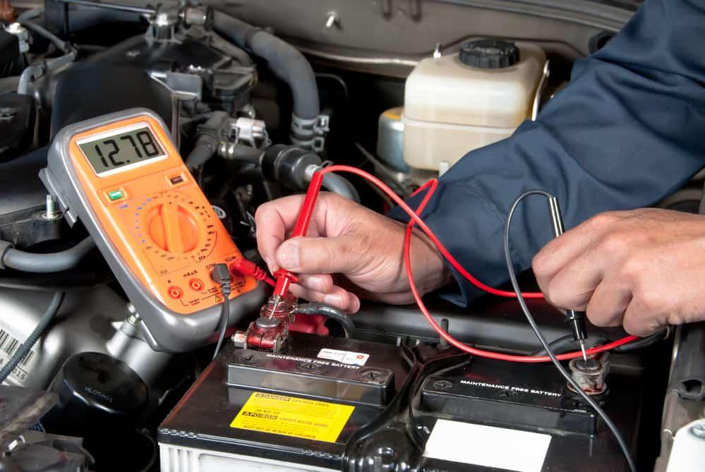 Auto mechanic checking car battery